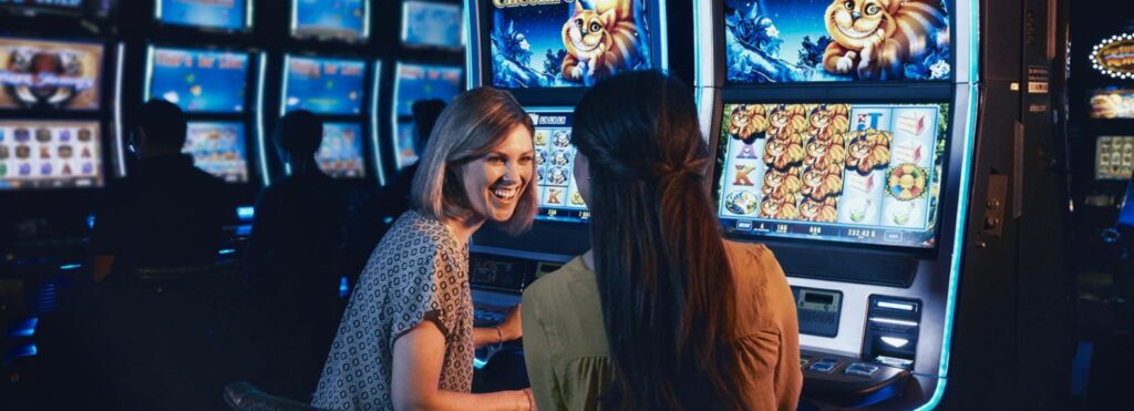 Two girls playing slots in Montreal casino.